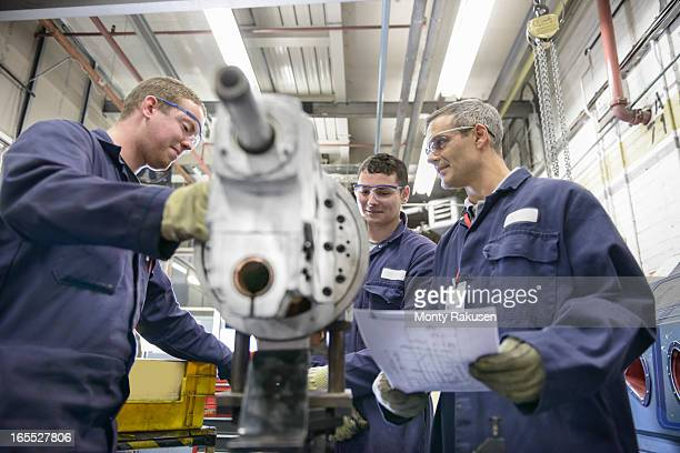 Engineer teaching apprentices wearing boiler suits in car plant