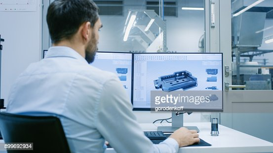 Engineer/ Technician Working on a Personal Computer with Two Displays, He's Designing New Component in CAD Program. Out of the Office Window Components Manufacturing Factory is Seen. : Stock Photo