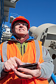 Engineer texting status on a mobile phone at materials plant in winter