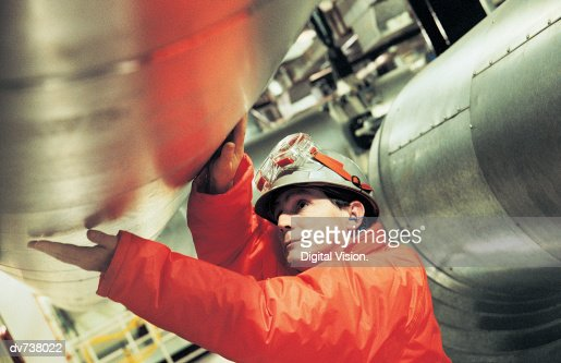 Engineer touching pipe in nuclear power station
