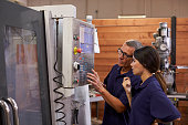 Engineer Training Female Apprentice On CNC Machine