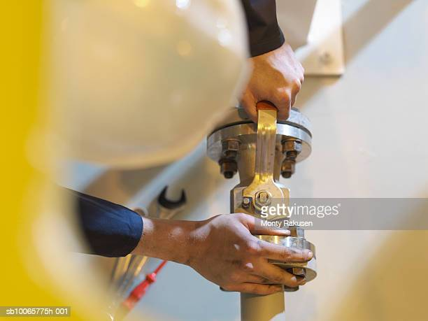 Engineer turning bolt with lever, close up of hands, directly above