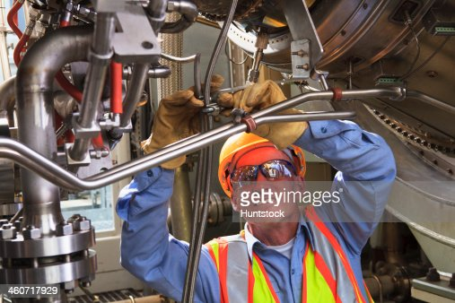 Engineer under ignitor stage of gas turbine which drives generators in power plant while turbine is powered down : Photo