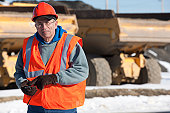 Engineer using a walkie-talkie in earth mover truck yard