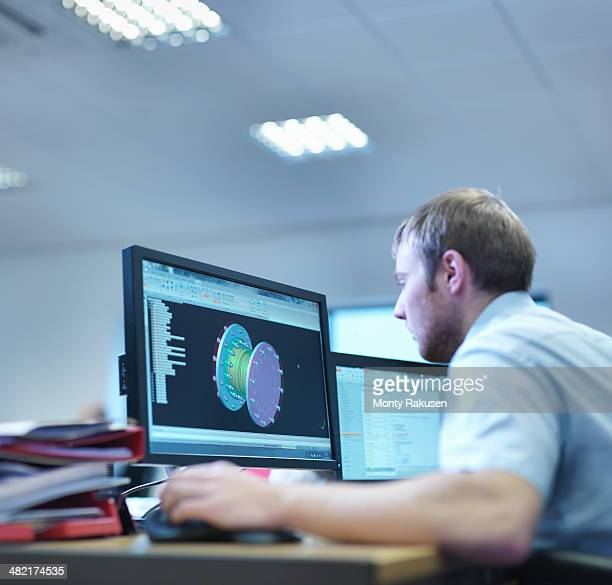 Engineer using computer aided design in factory office