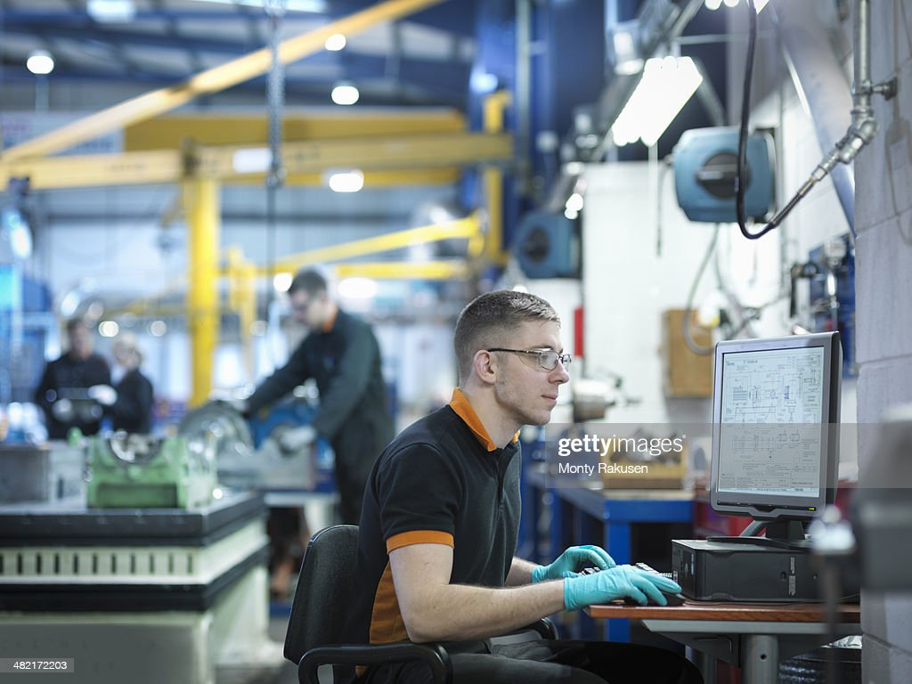 Engineer using computer in engineering factory
