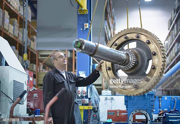 Engineer using crane to move large gear wheel in engineering factory