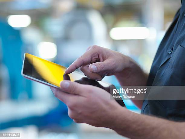 Engineer using digital tablet in factory, close up