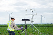 Engineer using tablet computer collect data with meteorological instrument to measure the wind speed, temperature and humidity and solar cell system on corn field background, Smart agriculture technol