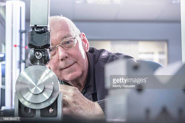 Engineer using tool to measure components in engineering factory