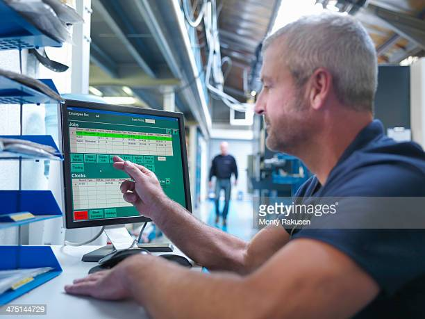 Engineer using touchscreen at computer workstation in factory