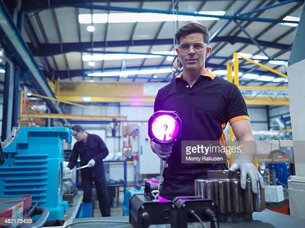 Engineer using ultraviolet light to test for cracks in gear wheel, portrait