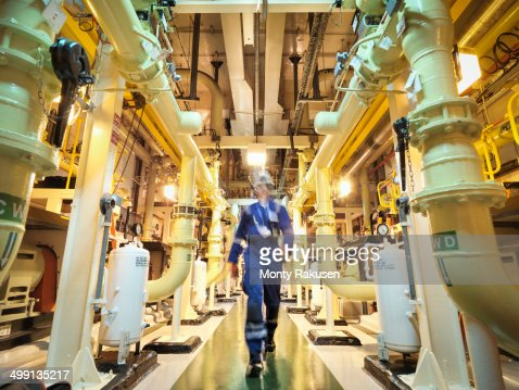 Engineer walking amongst pipes of nuclear power station