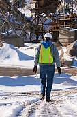 Engineer walking to sand and gravel conveyor at a construction site