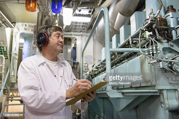 Engineer wearing ear defenders making notes in ship's engine room