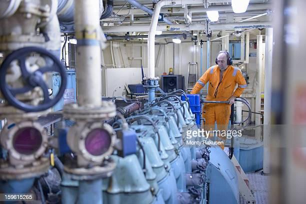 Engineer wearing ear defenders working in engine room on tug