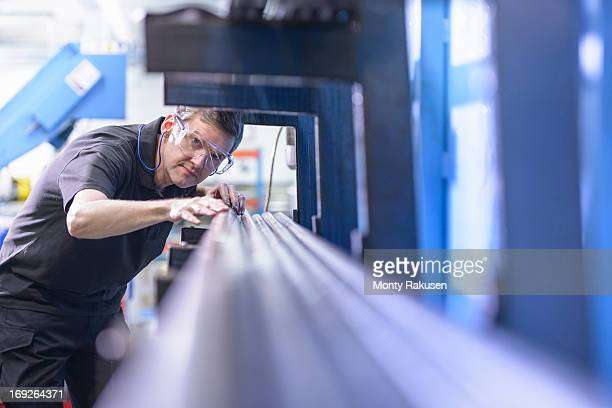 Engineer wearing safety glasses and inspecting steel rods