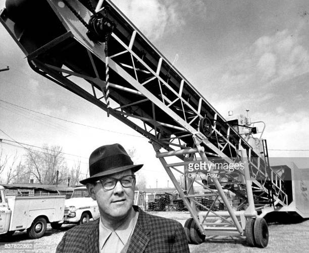 MANAGER AND 'GROUNDHOG Engineer who designed new conveyor stands in front of his 'brainchild' Credit Denver Post