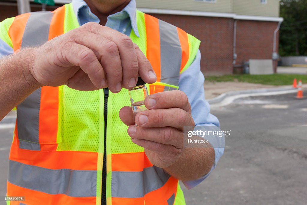 Engineer with a water sample from a street hydrant