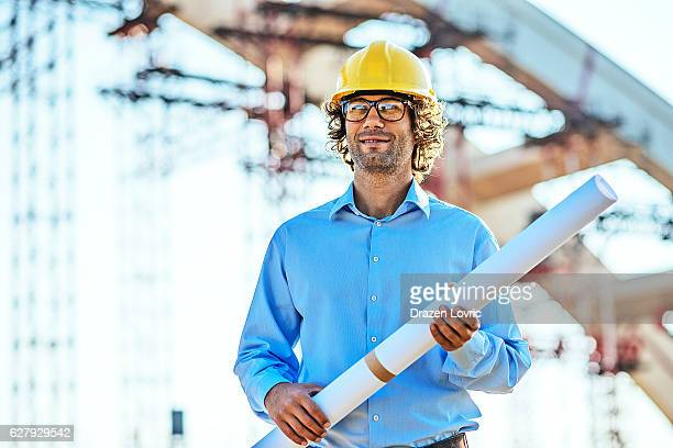 Engineer with blueprint standing next to construction platform