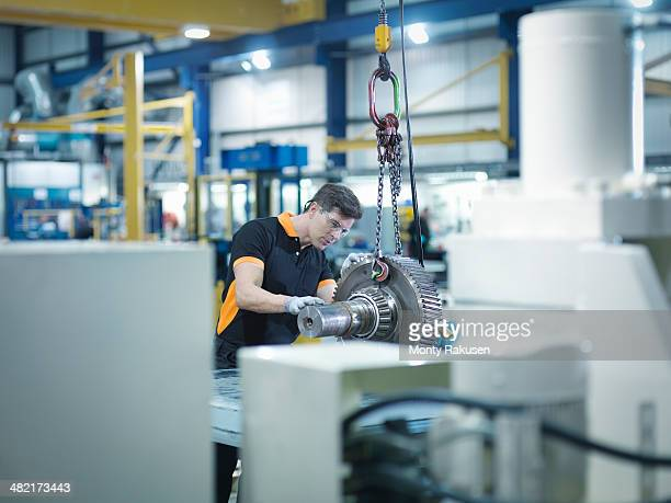 Engineer with gear wheel at work station in factory