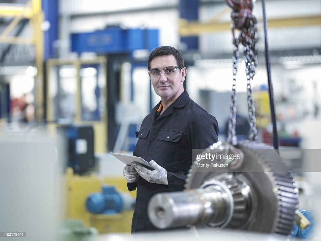 Engineer with gear wheel at work station in factory, portrait