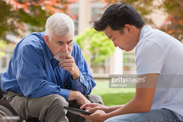 Engineer with muscular dystrophy and diabetes in his wheelchair talking with design engineer using tablet