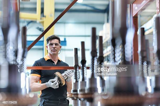 Engineer with parts in industrial gearbox factory, portrait