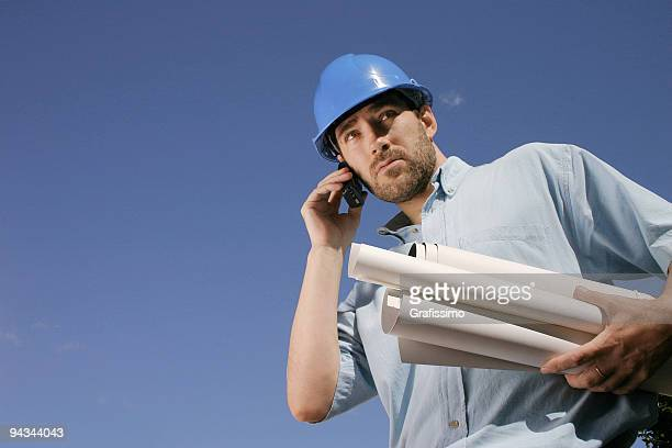 Engineer with phone and blueprints