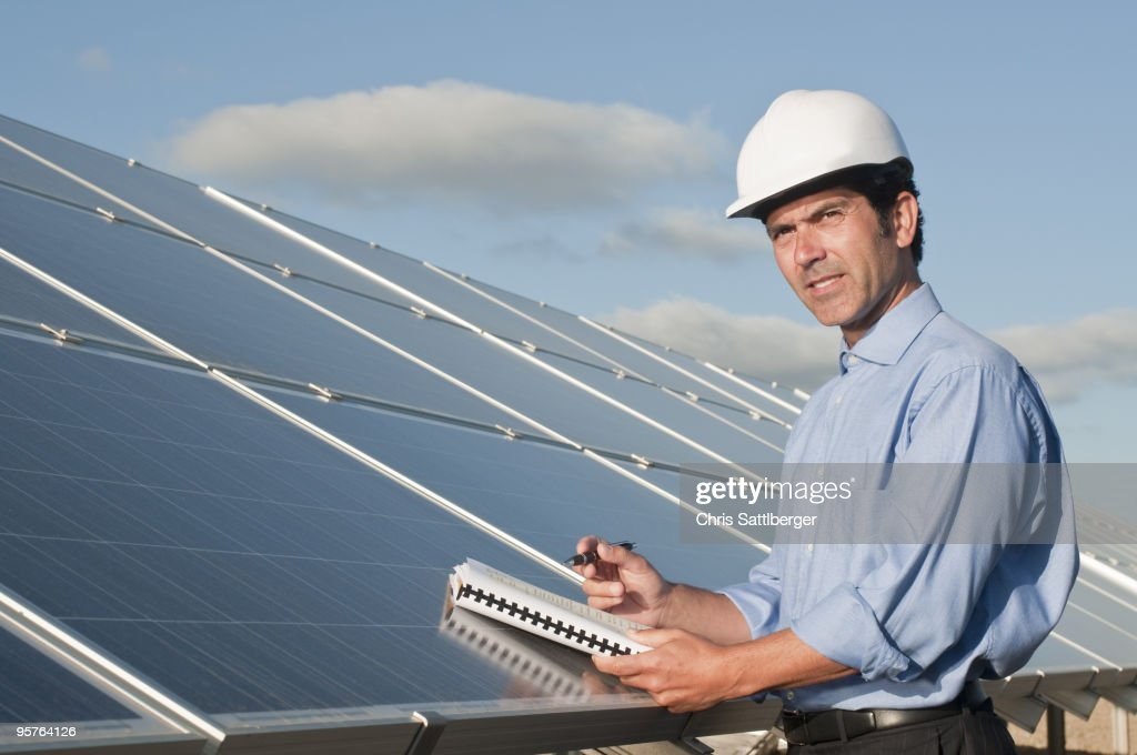 engineer with plans and solar panels : Stock Photo