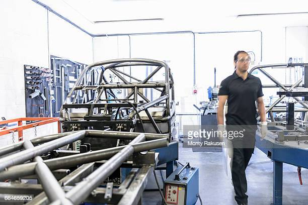 Engineer with racing car roll cages in racing car factory
