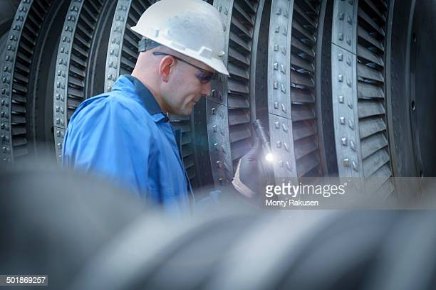 Engineer with torch inspecting turbine during power station outage