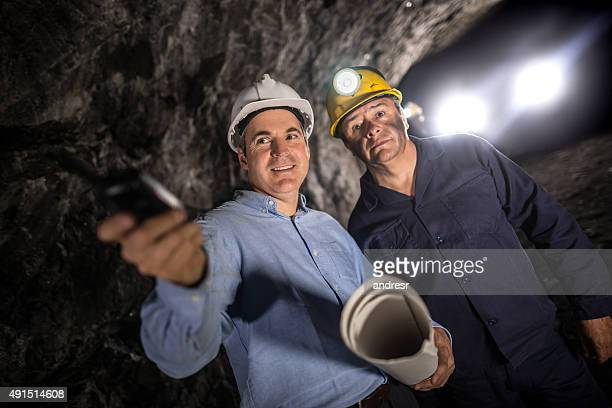 Engineer working at a mine and talking to a miner