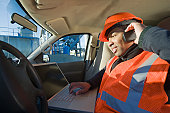 Engineer working on a laptop and talking on a mobile phone in a car