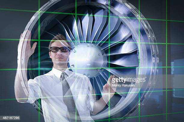 Engineer working with 3D display of Jet Engine, seen through interactive display
