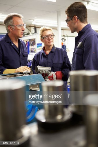 Engineer Working With Apprentices On Factory Floor : Stock Photo