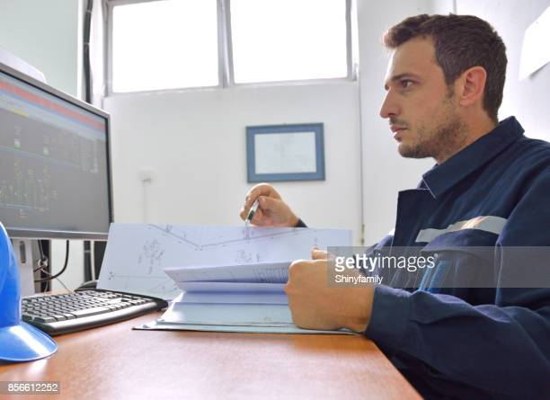 Engineer working with blueprints at the desk