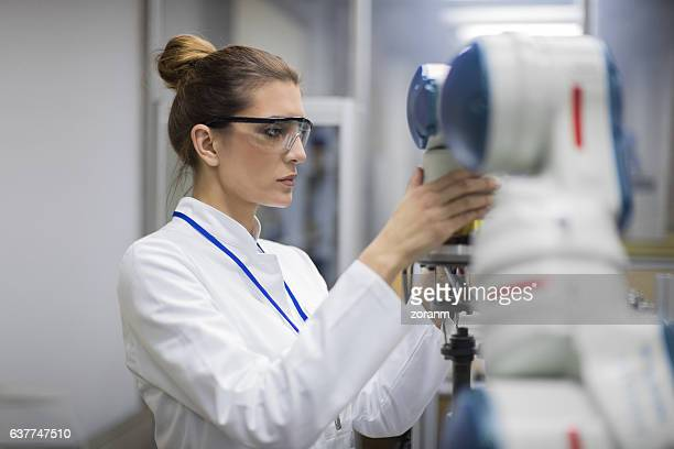 Engineer working with robotic arm in lab