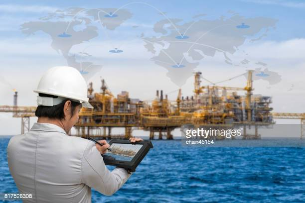 Engineer working with tablet PC near Oil and gas jack up drilling rig in the ocean sea from oil and gas industrial petroleum.