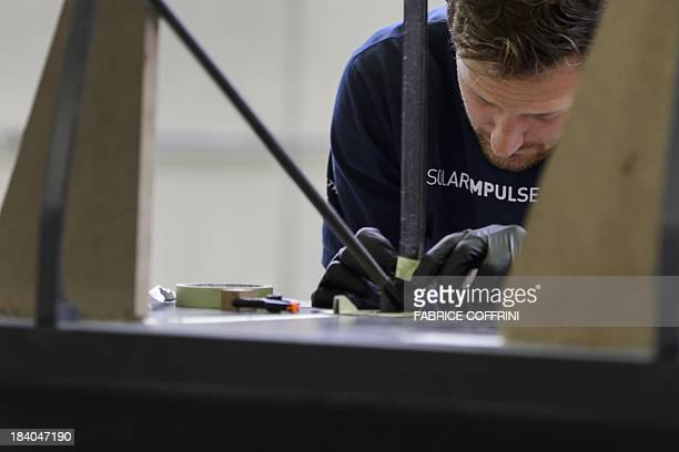 A engineer works on the carbonfibre 72 metres long wing of Swiss sunpowered aircraft Solar Impulse HBSIB on October 11 2013 in construction at former...
