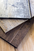 engineered tongue in groove hardwood floor planks of various styles and finishes in a stack