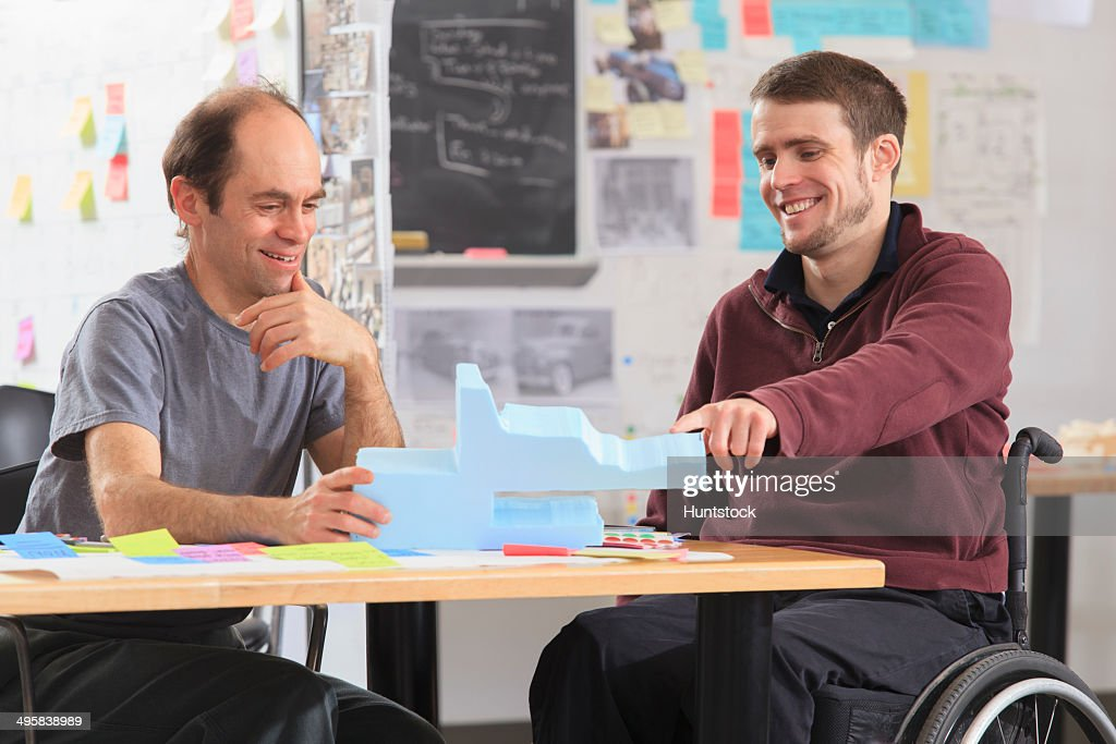 Engineering instructor with Aspergers discussing 3D shape with student in a wheelchair with a spinal cord injury : Stock Photo