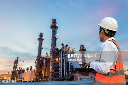 Engineering is use notebook check and standing in front of oil refinery building structure in heavy petrochemical industry : Stock Photo