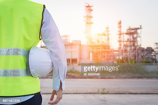 Engineering man standing with white safety helmet near to oil refinery : Stock Photo