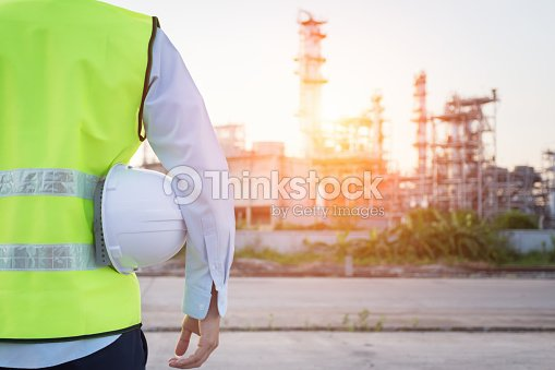 Homme de génie debout avec un casque de sécurité blanc près de raffinerie de pétrole : Photo