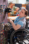 Engineering student in wheelchair examining wiring of a industrial control trainer