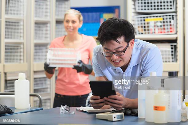 Engineering student using a tablet to record data in chemistry laboratory