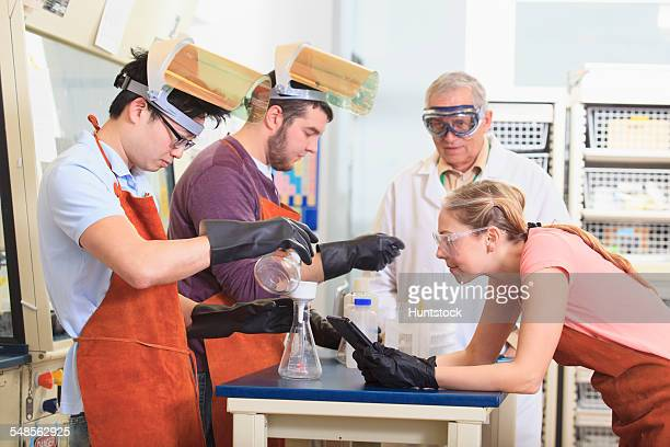 Engineering students and professor wearing protective equipment while working in chemistry laboratory