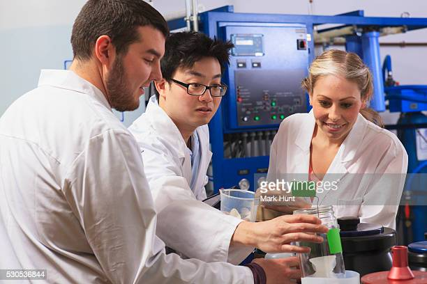 Engineering students examining liquid containers in water ultra purification system room in a laboratory