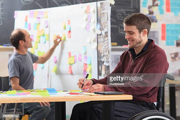 Engineering students posting brainstorming ideas on project board, one man with spinal cord injury and other one with Aspergers